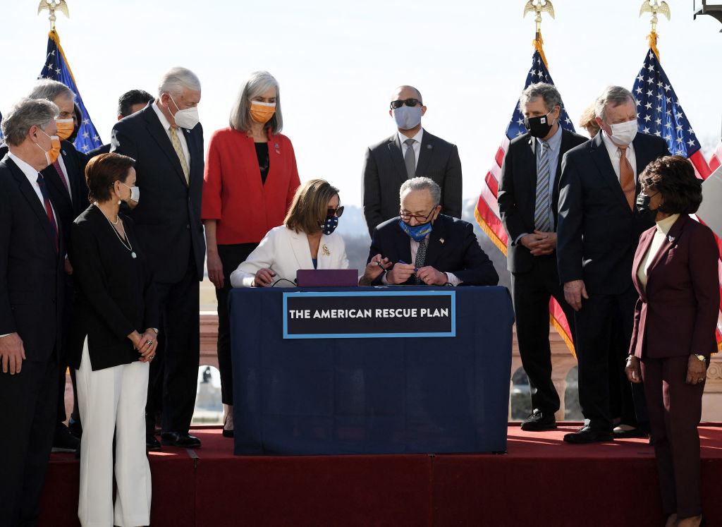 Speaker of the House Nancy Pelosi and Senate Majority Leader Chuck Schumer sign the American Rescue Plan Act after the House Chamber voted on the final revised legislation of the $1.9 trillion spending plan, at the U.S. Capitol on March 10, 2021 in Washington, DC. Jared Golden of Maine was the only Democrat to vote nay on the bill.