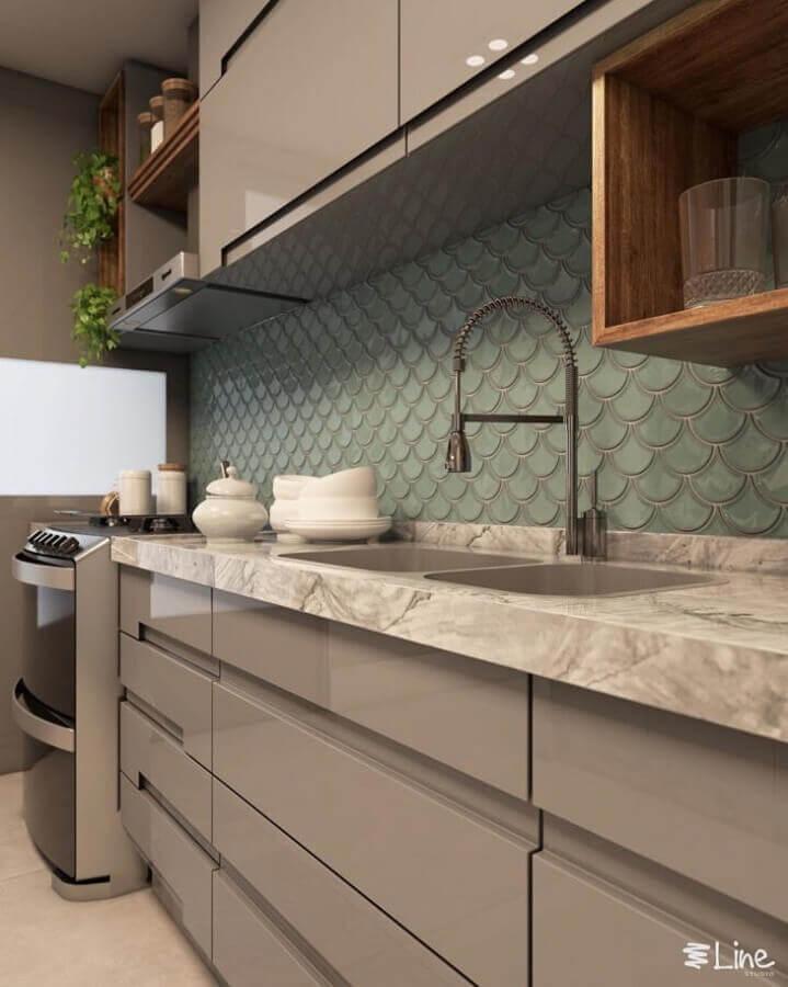 Cozinha com azulejo verde em estilo 3D, armários na cor cinza com detalhes de madeira