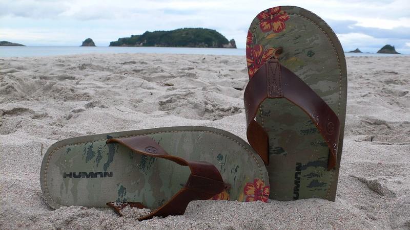 men's flip flops stuck in a sandy beach