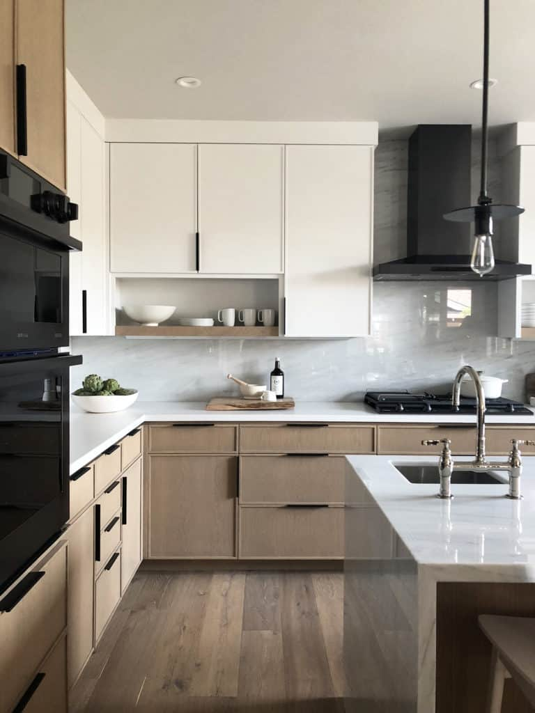 modern kitchen with white and brown cabinets, matte black modern cabinet hardware, glossy white backsplash and black appliances