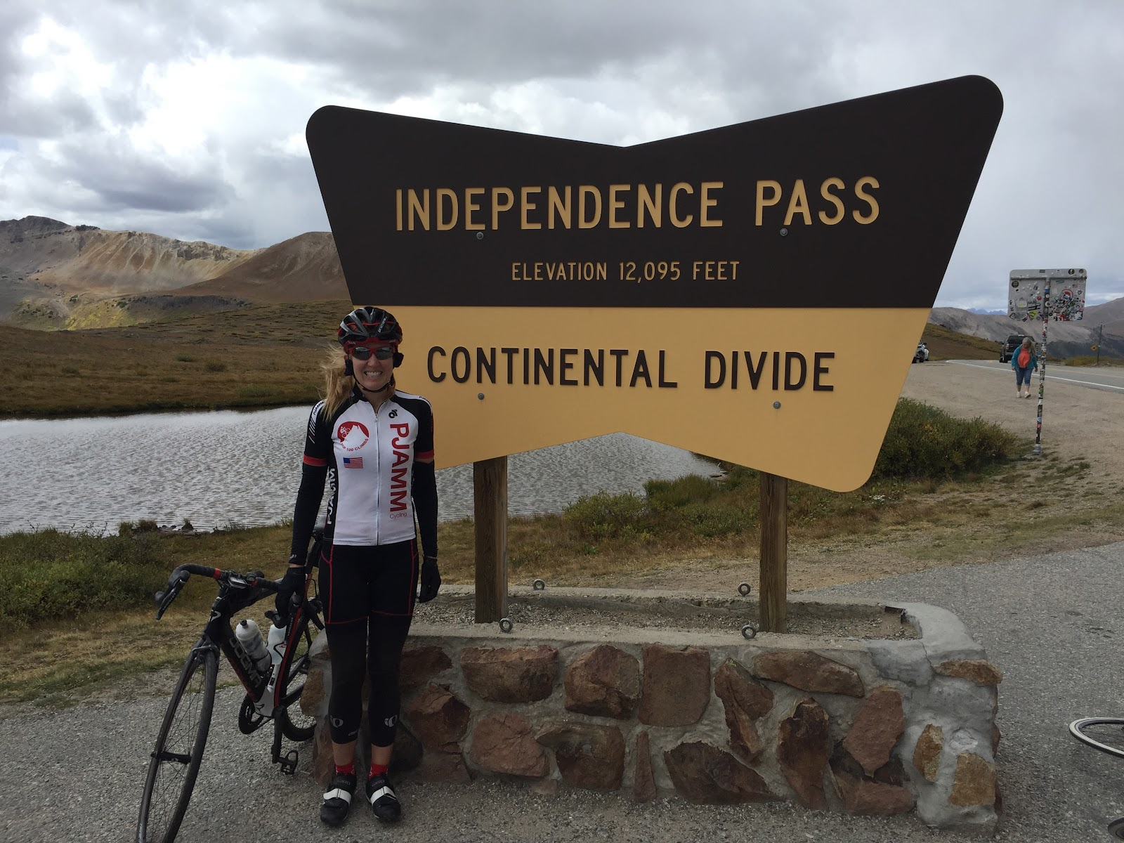 Bike climb of Independence Pass - Continental Divide sign and PJAMM cyclist Stacy Topping