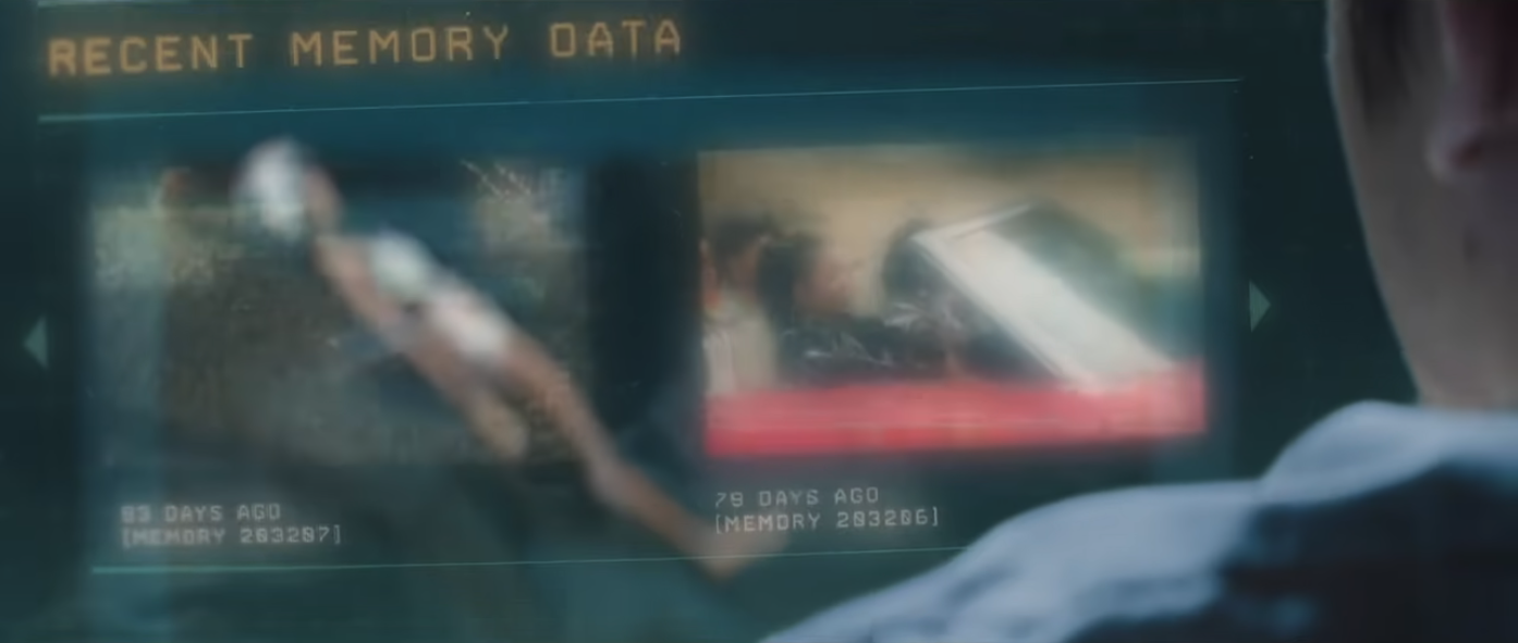 """A computer screen seen over the holder of a white person. """"Recent Memory Data"""" is seen on screen, along with still images and dates indicating memories. Jane, who is on the floating table in the room in front of them, can be partially seen behind the semi transparent screen."""
