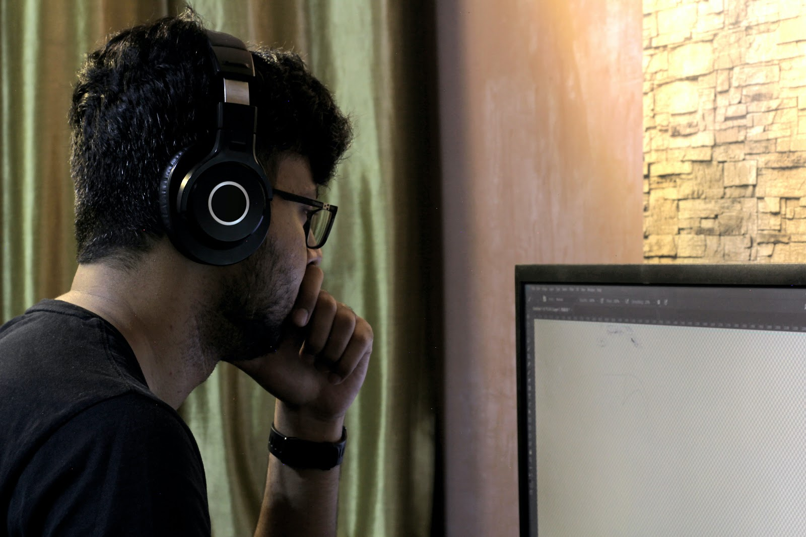 man with headphones looking at computer screen