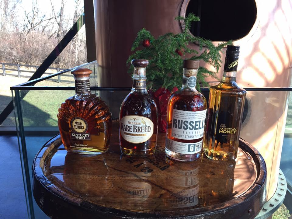Wild Turkey Kentucky Spirit, Wild Turkey Rare Breed, Russell's Reserve, and American Honey bourbons lined up on a whiskey barrel.