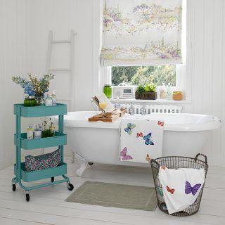 Phòng tắm màu trắng cổ điển với bồn tắm có chân đế và bộ lưu trữ xanh nổi bật
