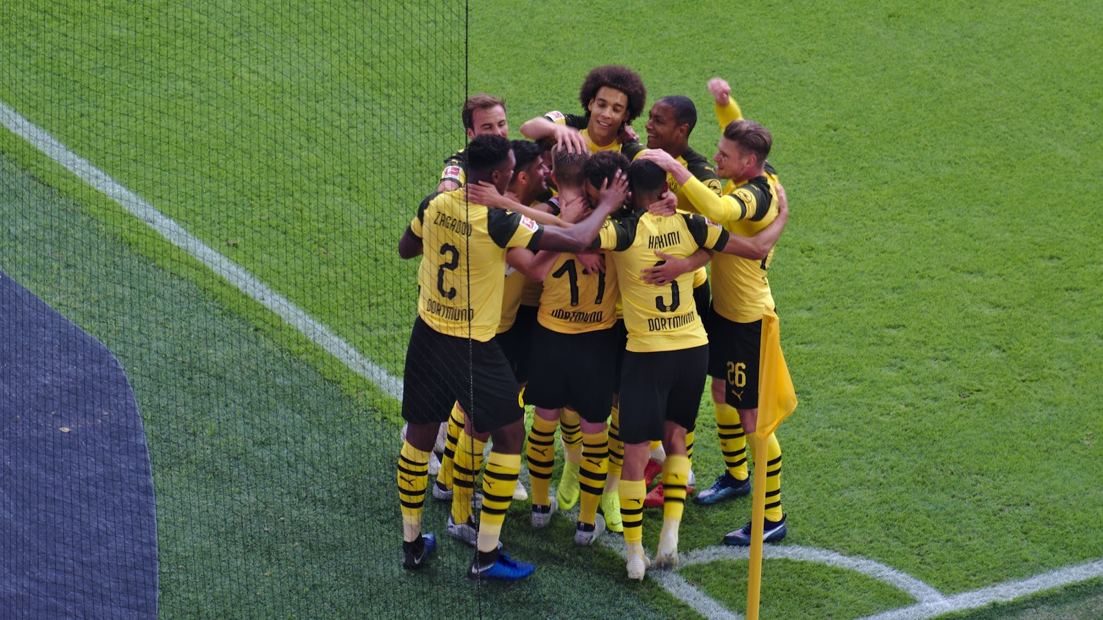 Borussia Dortmund players gather by a corner flag to celebrate a goal