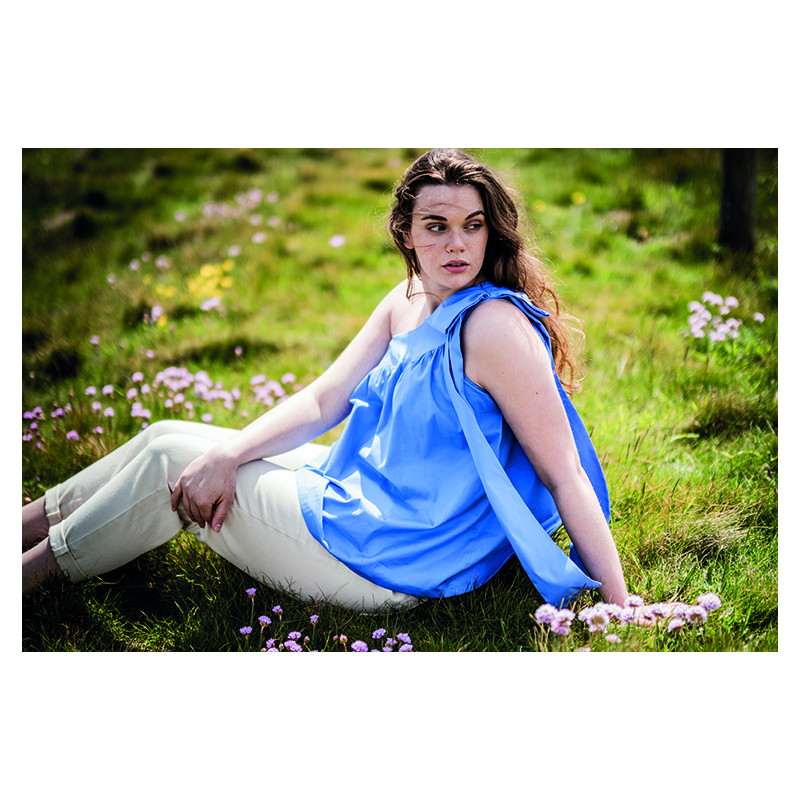 White woman sitting on grass wearing a blue top that ties on one shoulder and leaves the other shoulder is bare.   She is wearing light tan pants.