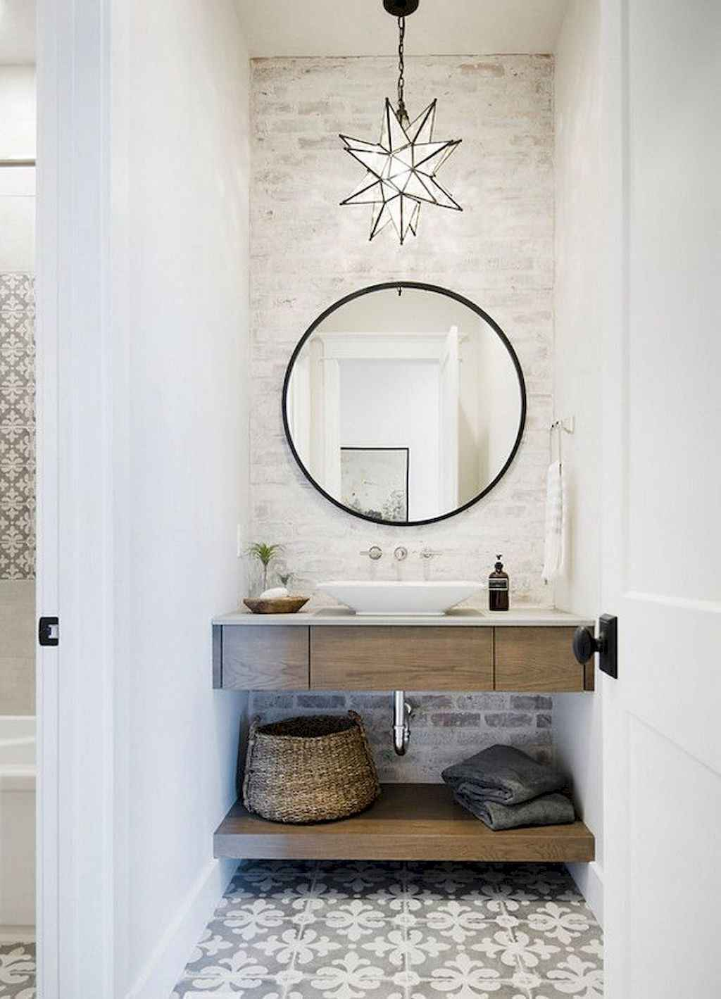 modern white bathroom with circular framed mirror, light wood vanity, patterned tile floor and star shaped pendant light