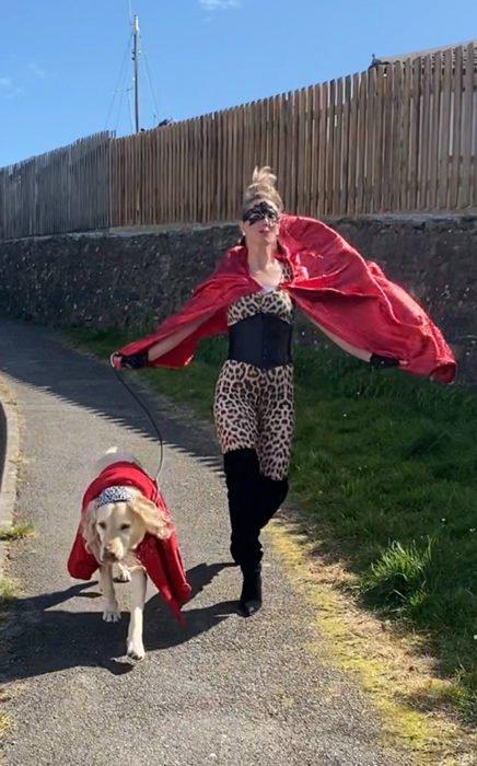 Mujer viste disfraz de superhéroe mientras paseo con su perro