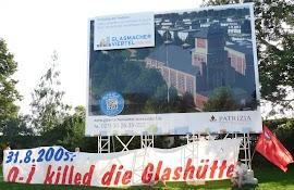 Vor der Schautafel »Glasmacher Viertel ›Im Geiste der Tradition‹« Transparent »31.8.2005: O-J killed die Glashütte«.
