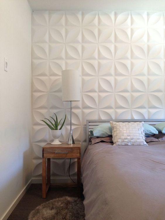 Quarto com parede da cabeceira com revestimento 3D, piso de madeira e criado mudo de madeira.
