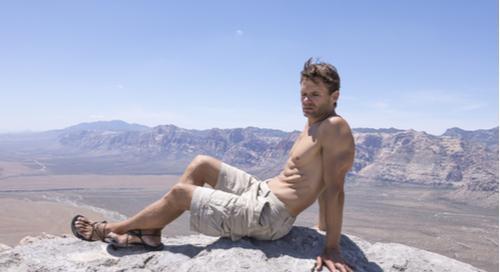 Muskulöser Mann in Cargo-Shorts auf Berggipfel