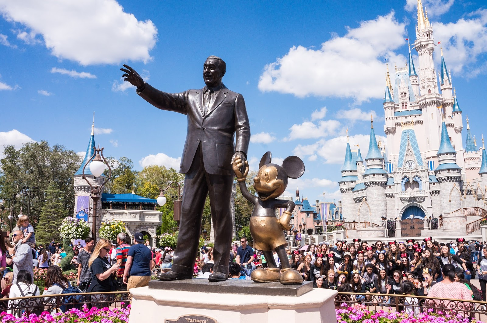 walt disney and mickey mouse partners black and gold statue in crowded walt disney world orlando theme park