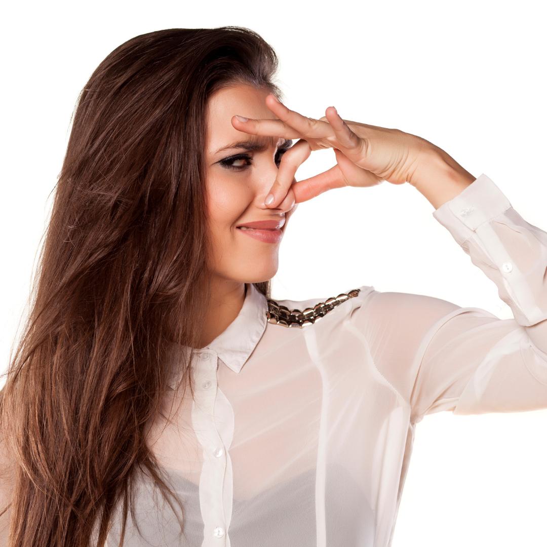 Une femme qui se bouche le nez à cause des mauvaises odeurs de ses WC