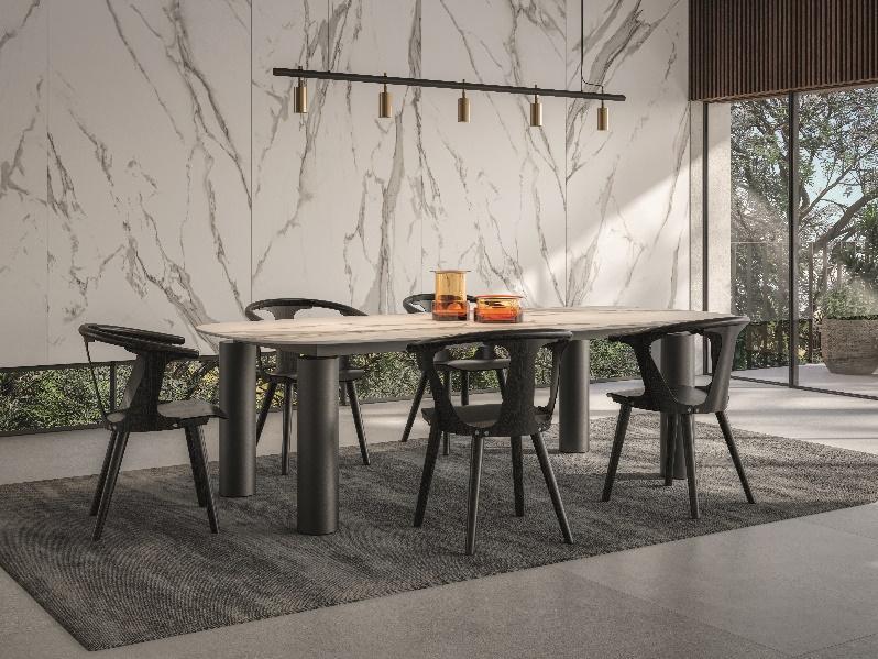 sala de jantar com porcelanato marmorizado na parede principal, piso cinza, mesa de madeira com estrutura cinza com 5 cadeiras, tapete cinza e luminária pendente cinza e dourado.
