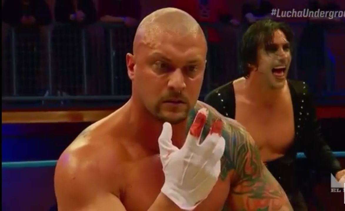 Screen cap from Lucha Underground. The focus of the image is Killer Kross, a bald white wrestler, holding up a hand. He is wearing a white glove with the first two fingers soaked with blood. He looks mesmerized at his own hand while Paul London laughs in the background.