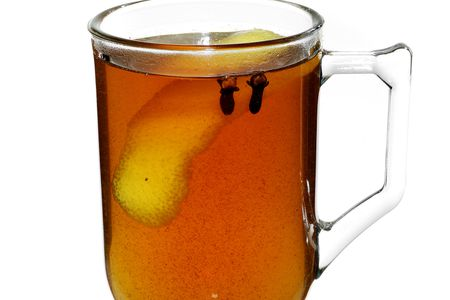 Glass filled with ginger hot toddy with lemon peel