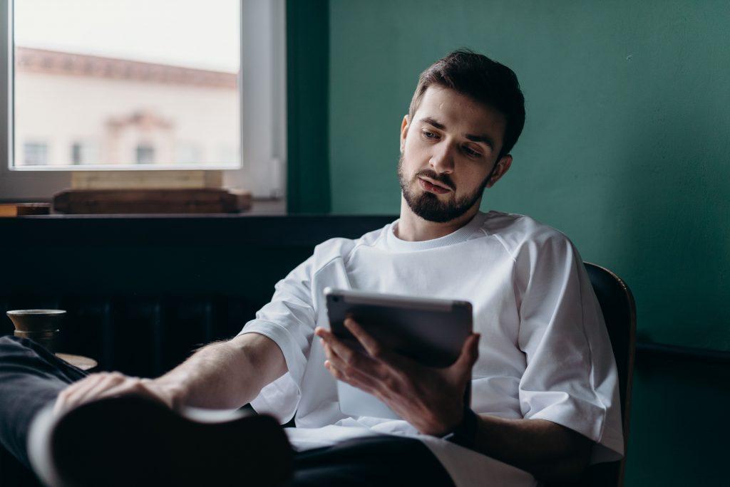 Homem sentado olhando um tablet durante compra online de lentes de contato