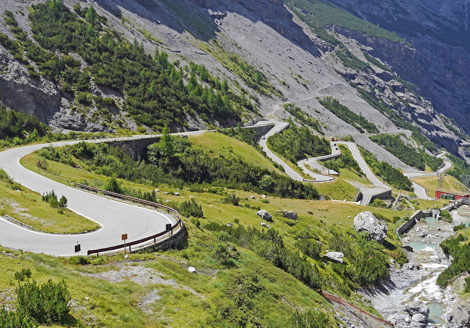 stelvio pass touge twisty uphill paved road in alps surrounded by green grass and stones