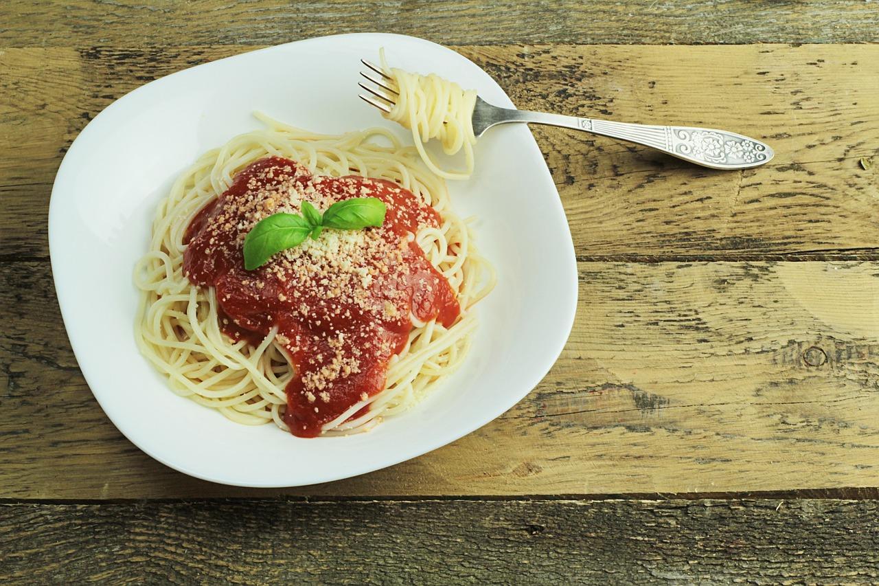 צלחת פסטה עם רוטב עגבניות פרמז'ן ועלה בזיליקום. עם מזלג