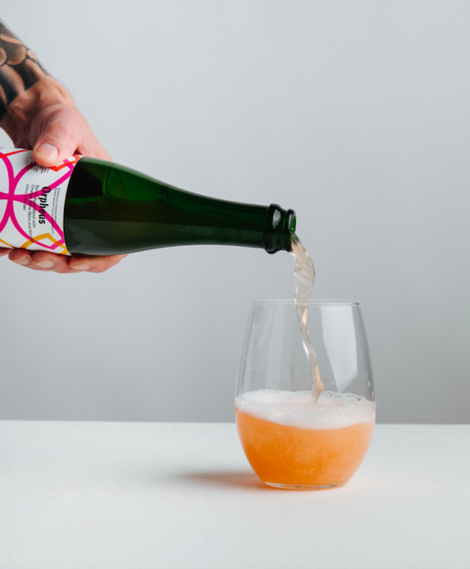 A bottle of Orpheus being poured into a round, stemless glass