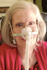 Photo of Diane Coleman wearing red print top and red sweater, smiling with gray bobbed hair, wire rimmed glasses and a nasal breathing mask