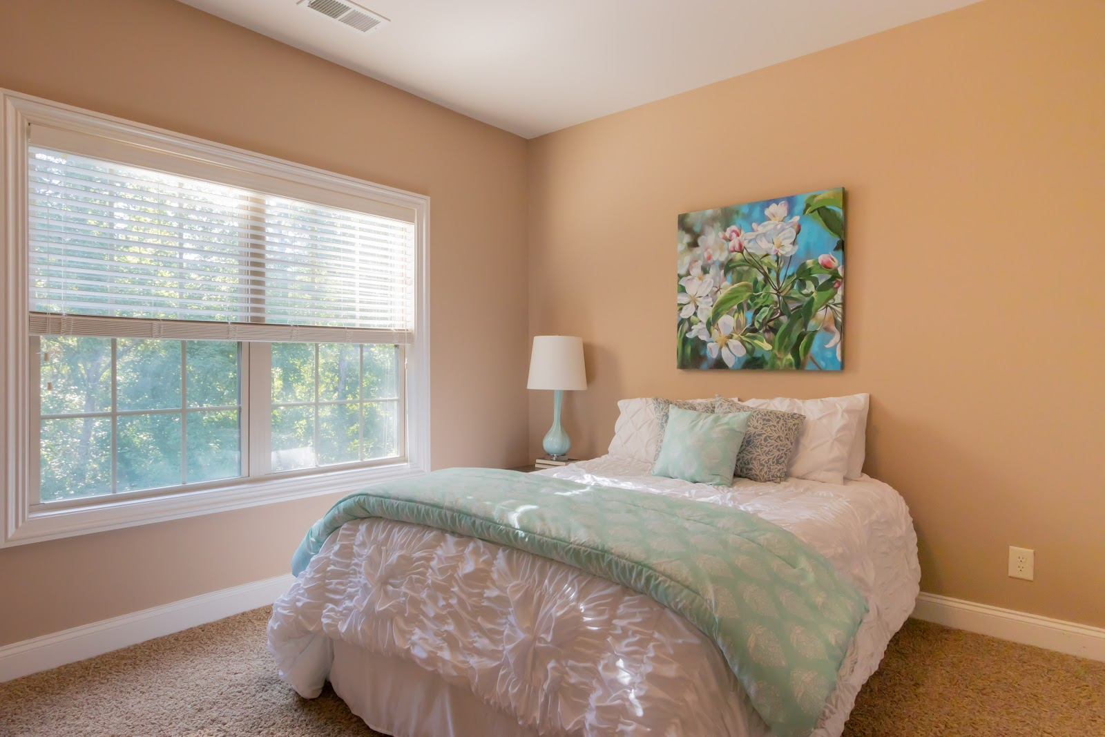When staging a bedroom be sure to use light bedding in a neutral color and plenty of space to walk around the room.