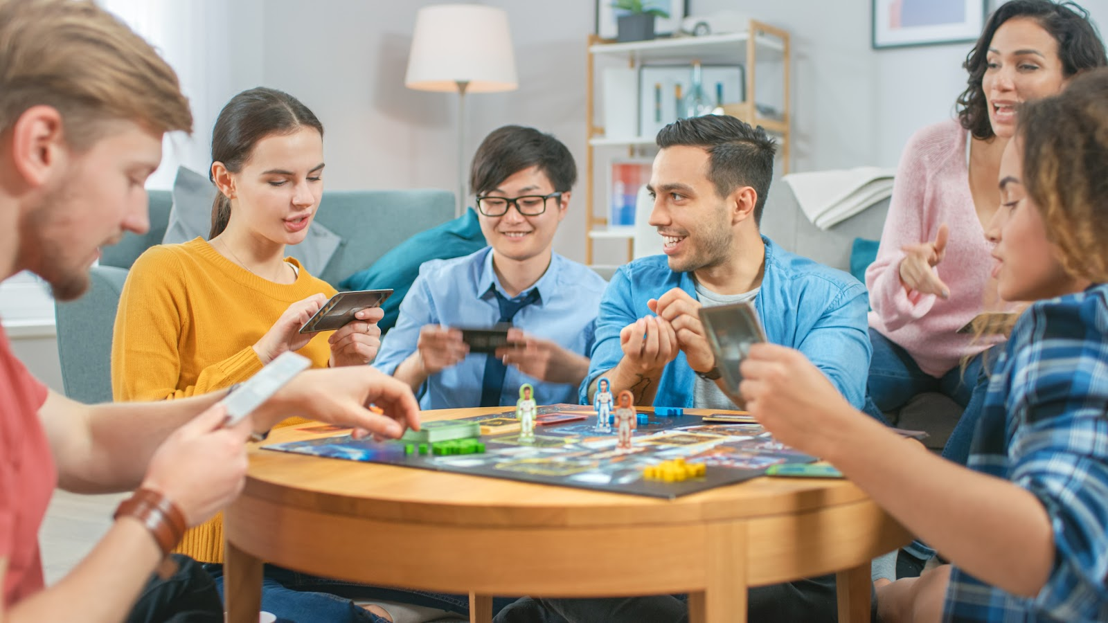 Six friends gather around a coffee table to play a board game.