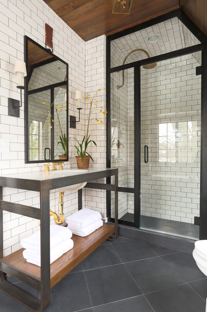 modern bathroom with white subway tile backsplash, black framed shower, grey floor tile