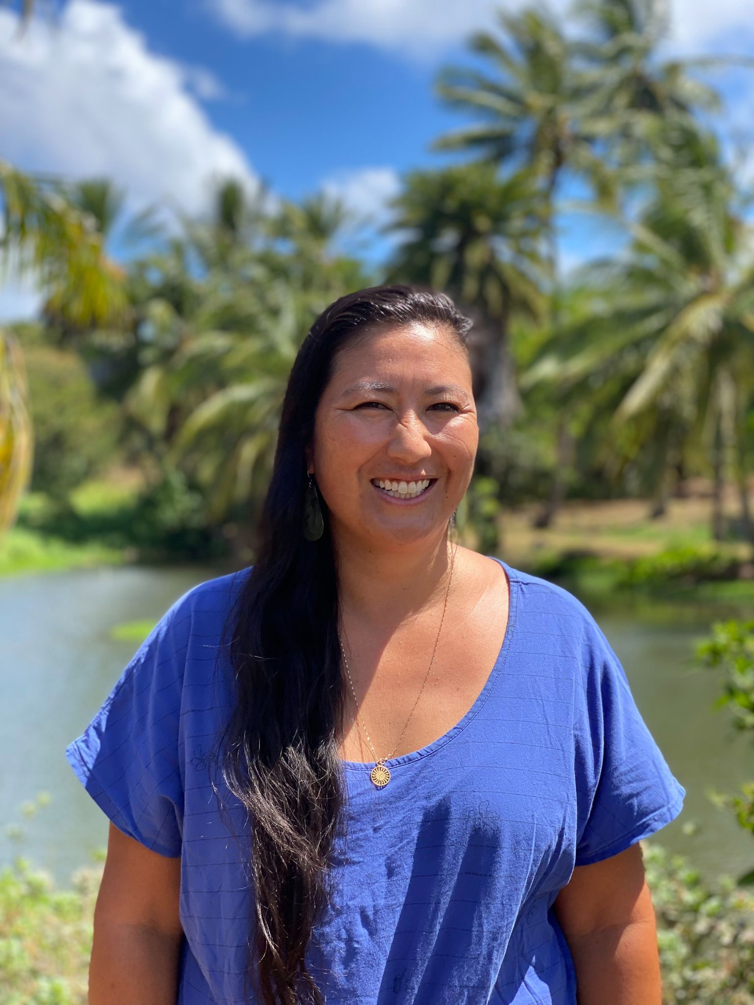 A woman with long, dark hair in a blue shirt smiles at the camera in front of a pond and palm trees.