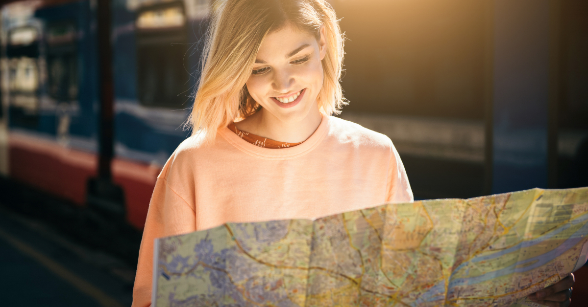 A short-haired blonde woman looking at a map in a train station
