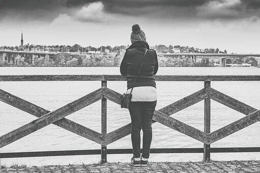 woman on a bridge looking into the horizon