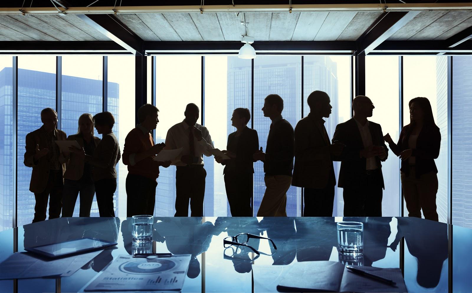 Funcionários de empresa conversam em sala de reunião.