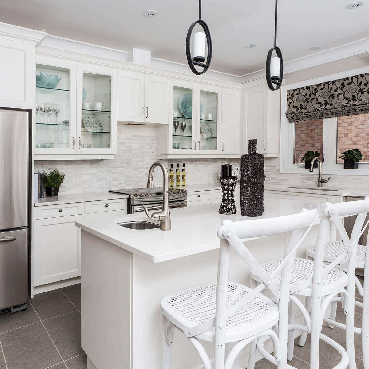 bright white kitchen fitted with white shaker cabinets. some of the shaker cabinets have glass doors, displaying dishware and decor inside. to match the cabinets, a bright white island with white countertops and matching chairs sits in the center of the room