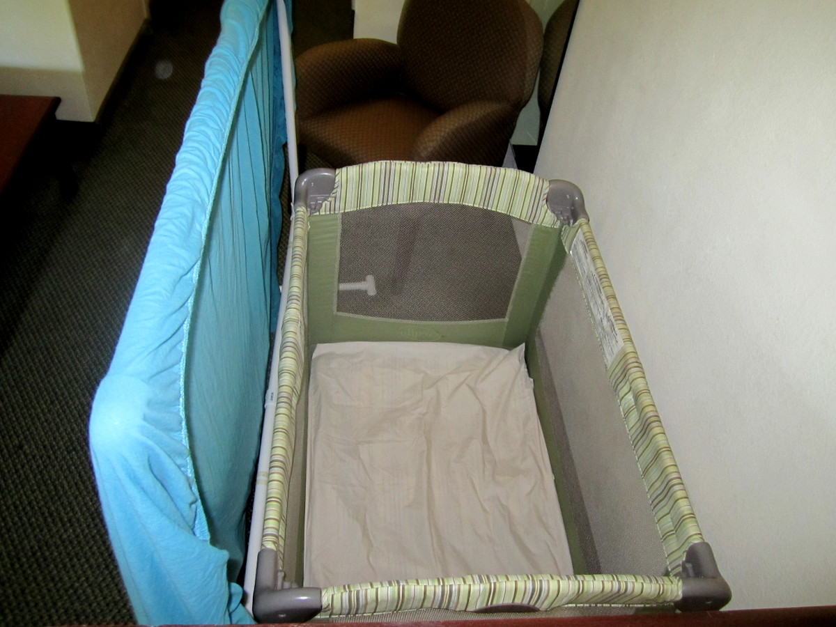 hotel room set up with portable crib and divider so young kids can sleep during a road trip stopover
