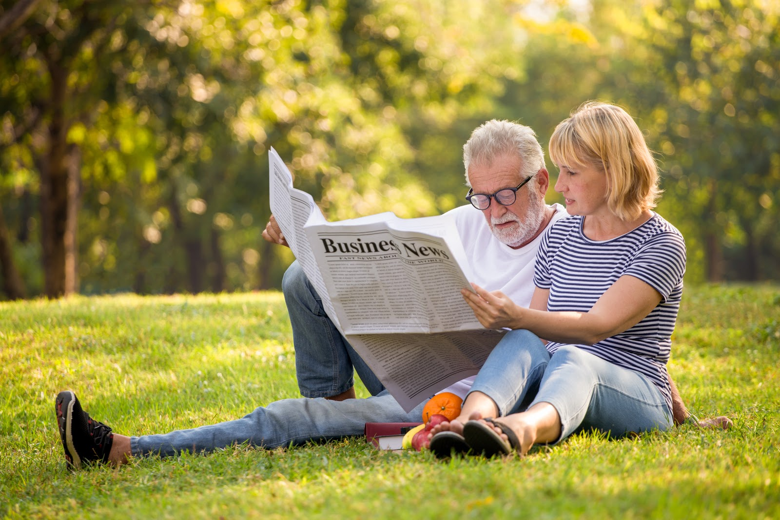 dividend investing: old man and woman reading a newspaper outside