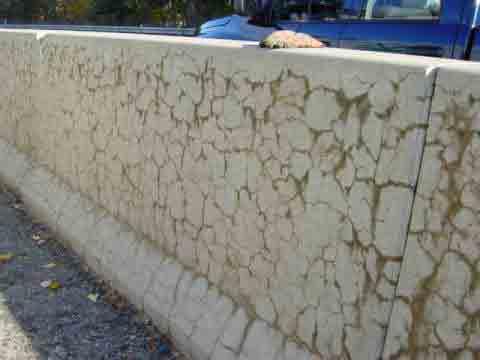 Muro externo em concreto, altamente fissurado, sem direção definida.