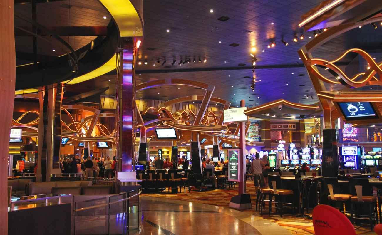 Inside of a casino lit up with lights from casino games and TVs