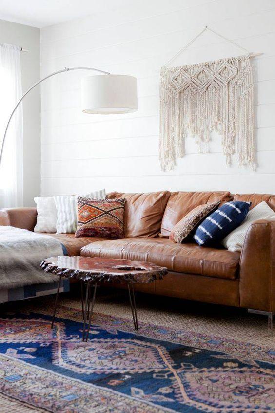 Sala de star com sofá marrom com almofadas coloridas, tapete, mesa de centro, abajur e macramê pendurado na parede.
