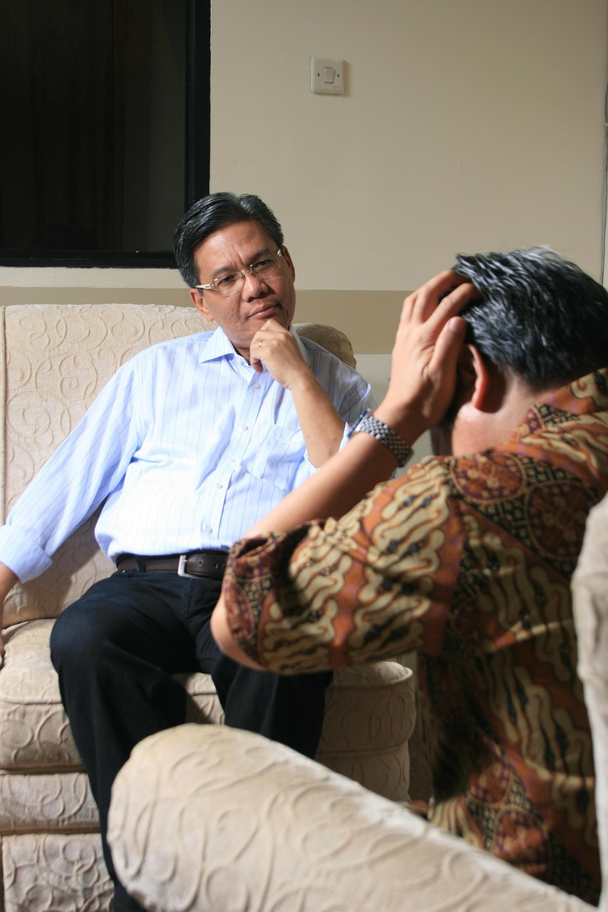 A counselor listens to his patient in a talk therapy session