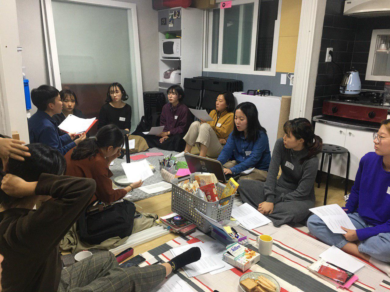 그림1: 활동가들이 사무실 바닥에 모여 앉아있다. 세미나 참고 자료는 바닥에 놓여있거나 활동가의 손에 쥐여 있다. 세미나를 진행하는 다희가 말하고 있고, 다른 활동가들의 시선은 다희를 향하고 있다.