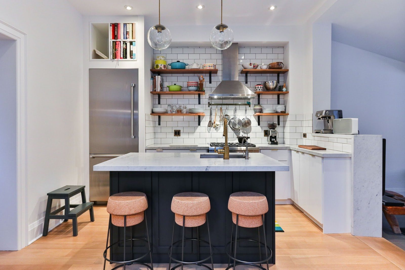Open-plan kitchen with open shelves, bowls, stovetops, and other utensils in the background