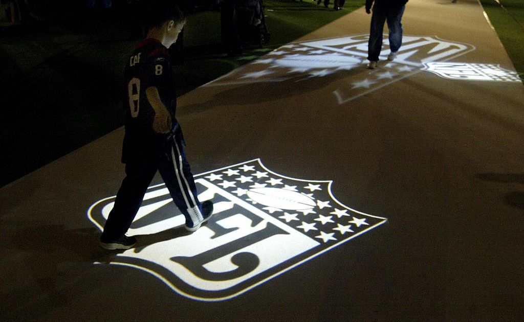 A young football fan walks on the projected logo at NFL Experience