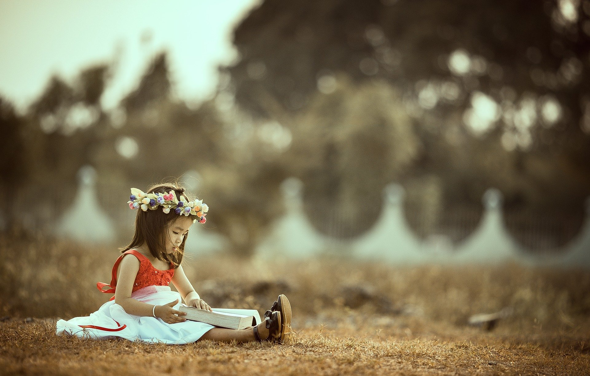 Child sitting on the ground reading.