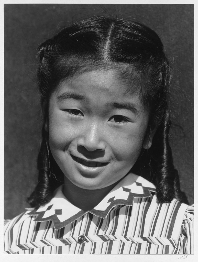 A portrait of Joyce Okazaki as a girl in Manzanar. She is smiling and looking at the camera, wearing a striped dress and her hair curled in ringlets.