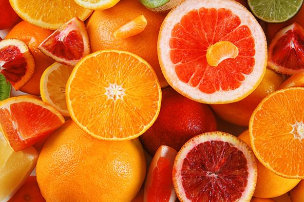 Several citrus fruits, primarily oranges, sitting in a pile
