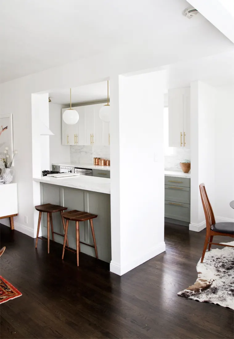 galley kitchen remodel with a large hole cut into the wall, serving as a breakfast nook. white and grey shaker cabinets fill the back wall of the bright modern kitchen
