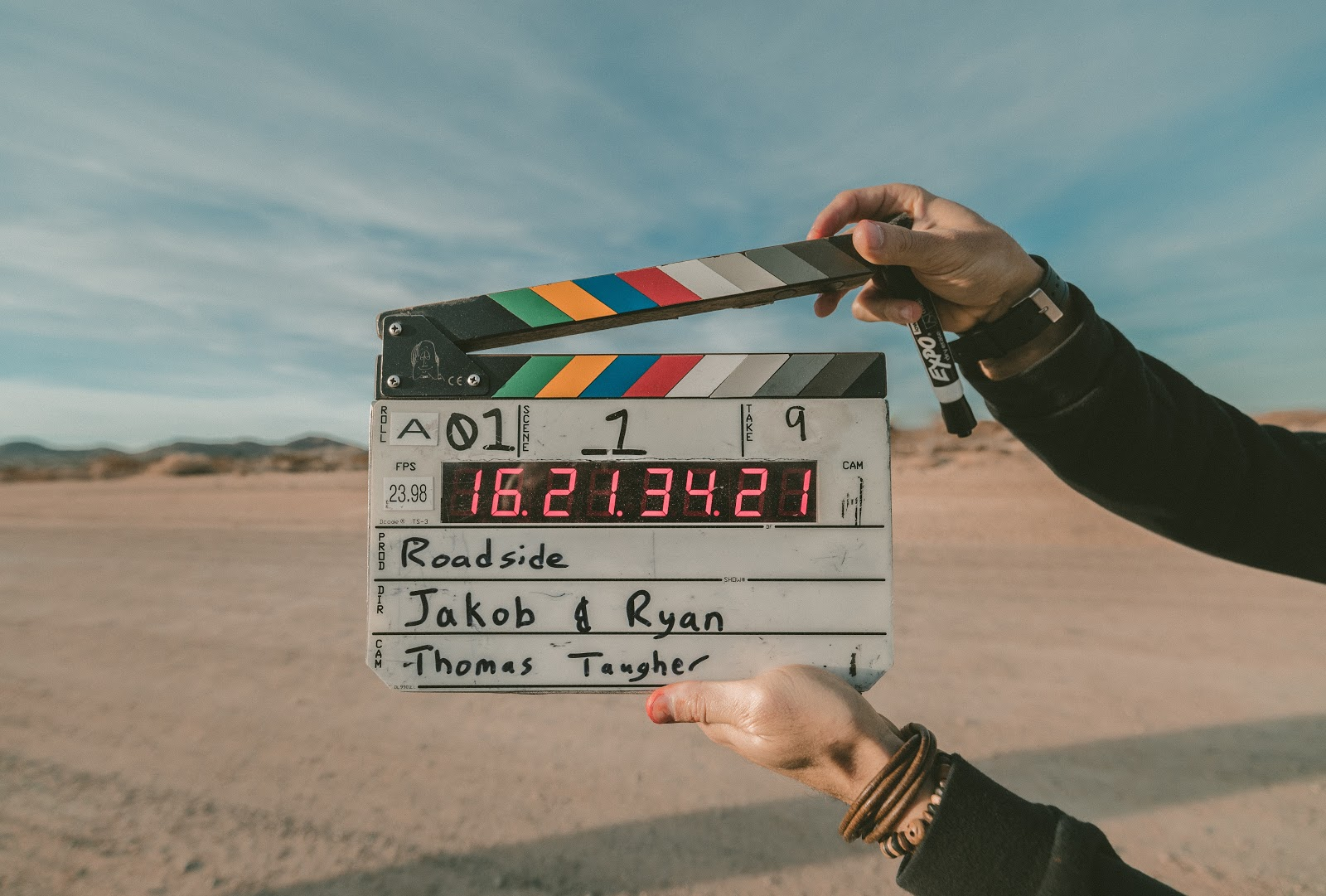 A set of hands is holding a movie clapperboard in front of an empty desert scene.