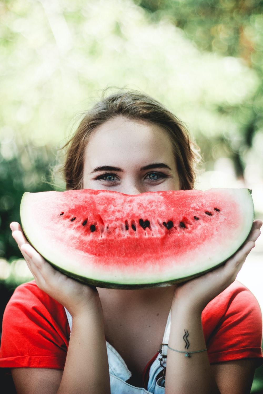 woman holding sliced watermelon