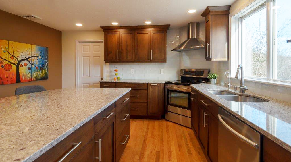 A large kitchen with stainless steel appliances and wooden cabinets  Description automatically generated
